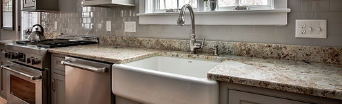 Granite kitchen counters with and apron sink and subway tile backsplash in one of our home remodel