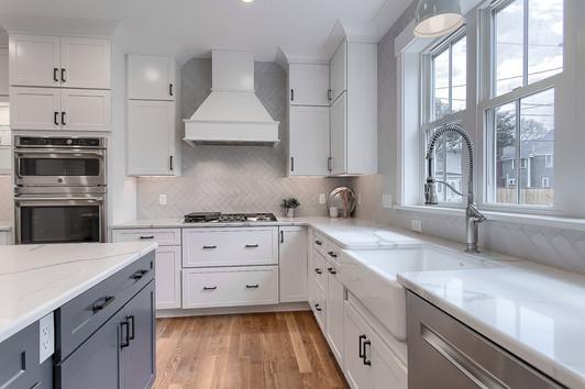 White Apron Sink With Custom Herringbone Style Backsplash
