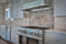 Custom stone backsplash behind kitcen range