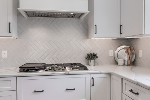White Quartz Counters and a Herringbone Backsplash