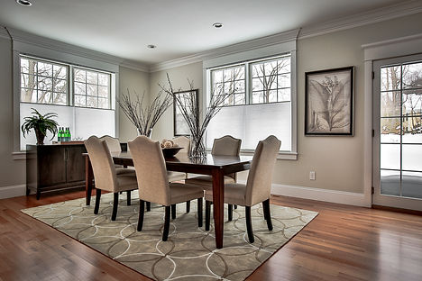 a bright dining area with hardwood flooringand dark hardwood dining table