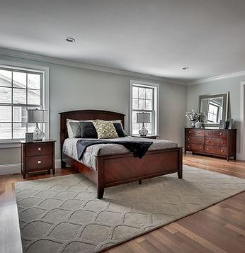 Master bedroom with dark wood furnirure and hardwood floors