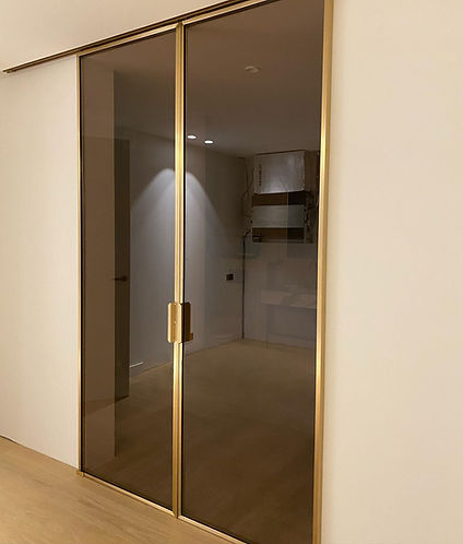 Portes en laiton massif brossé et patiné à la main et des verres couleur bronze