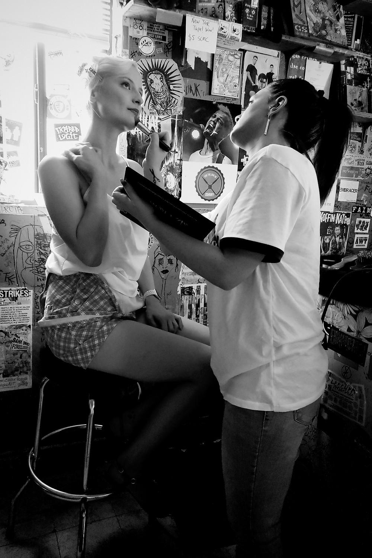 An actress has her makeup applied by a professional makeup artist