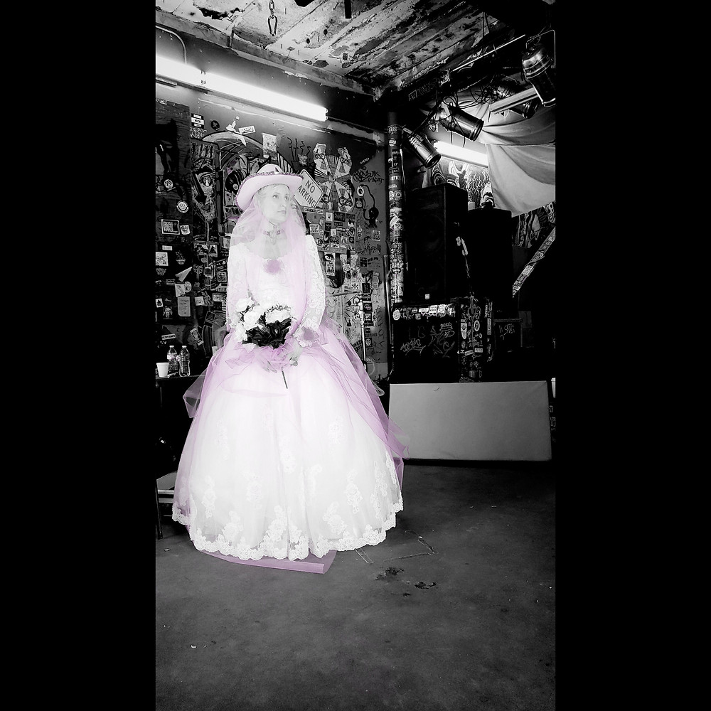 An actress in a wedding dress stands in a punk venue
