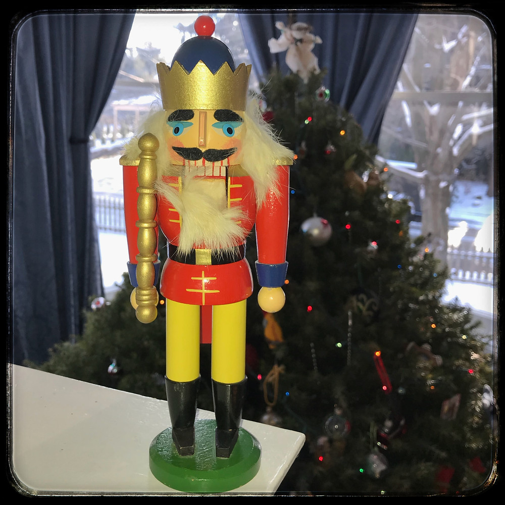 Nutcracker in front of Christmas tree on snowy day