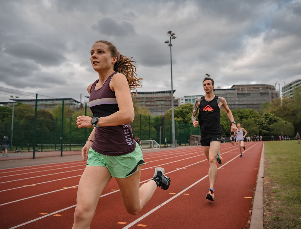 Jess Saunders of The Stable and Belgrave Harriers runs with Will Johnson on the Battersea Park Millennium Arena track