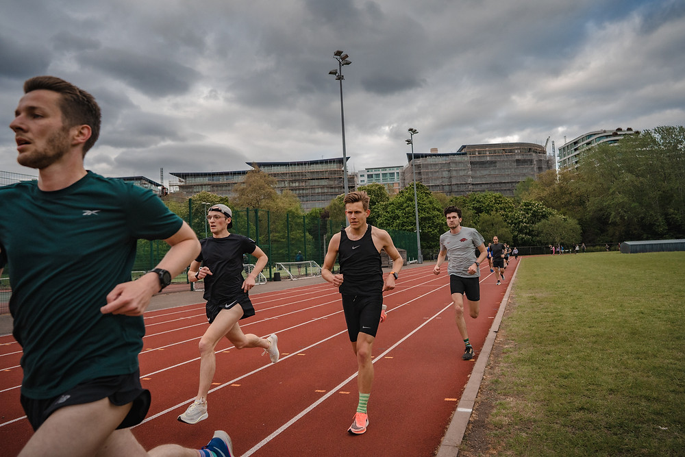 Belgrave men's team manager Steve Gardner leads Neil Wilson, Dylan Mitchard and Aidan Swaine on the track at Battersea Park Millennium Arena