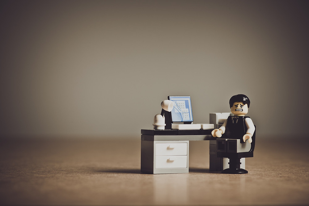 A stressed-out lego man sitting at a computer.