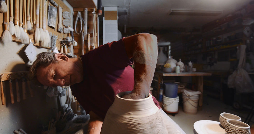 Steve Branfman, the film's subject, sits in front of the pottery wheel, making a bowl.