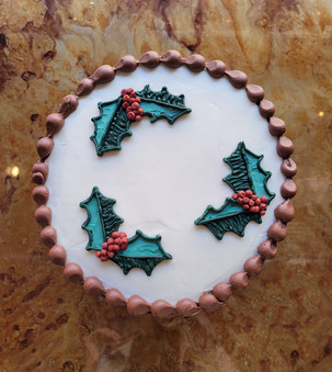 3 color full custom holly chocolate cake with vanilla buttercream frosting and chocolate buttercream shell border.