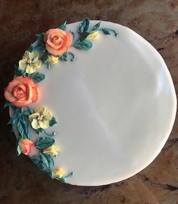 3 color half floral wreath vanilla cake with vanilla buttercream frosting.