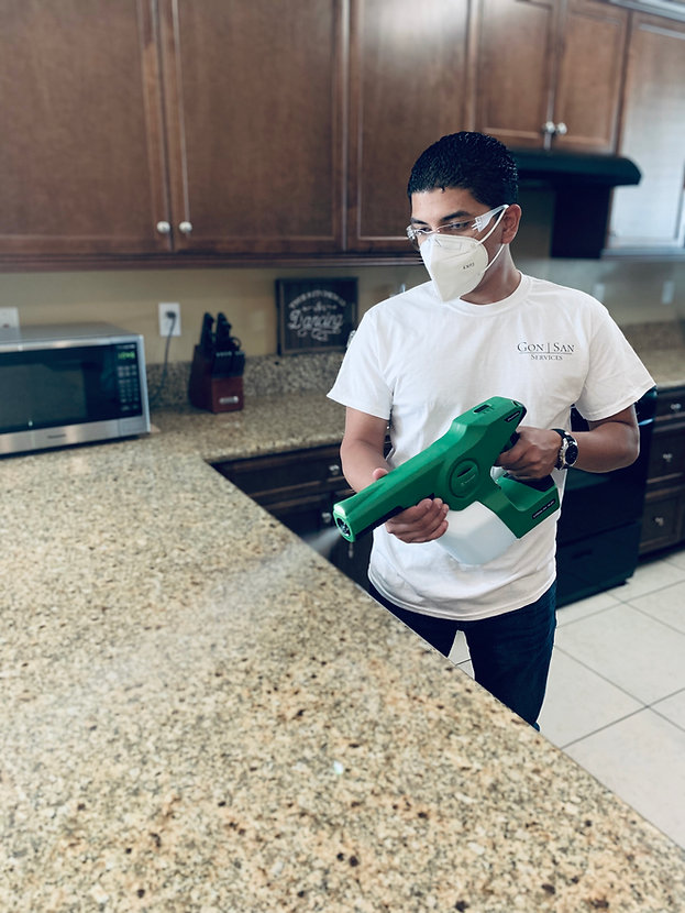 GonSan Services, your local luxury home cleaning service, is disinfecting a kitchen counter top.
