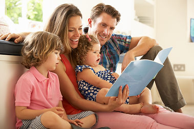 Parents Sitting With Children Reading St