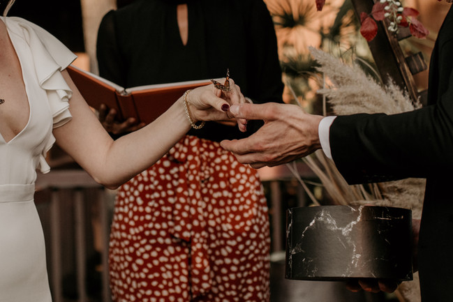 We can see a bride and groom with their hands close together. The bride has a monarch butterfly on her hand. Her nail are painted burgundy and she is wearing a gold chain bracelet. We can see very little of either of them, and we can see the officiant in a black blouse and red flow pants with white spots.