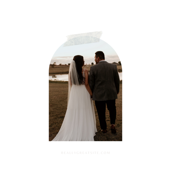 A bride and groom are facing away from the camera in a field with a small space of water in the back ground. The bride is wearing a lovely wedding dress, the top half ornated with jewels and the bottom a gorgous display of lace trailing behind her. Her hair is dark and sits at the base of her back, curled. Her veil is simple yet elegant. The groom is wearing a tux and his hair is dark and short.