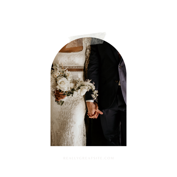 A bride and groom are the main focus of this image. We can only see their mid sections, the main focus of the image being their hands held in between them. The bride stands on the left with a bouquet in her right hand, and the groom on the left. The bride's dress is decorated with stunning embellishments.