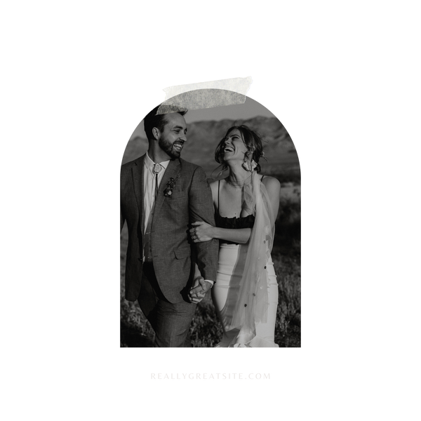 A black and white image of a man and woman, arms locked and smiles are wide and full of joy. The man is in a western style suit and the woman in a form fitted mermaid style skirt and dark top with thin straps.