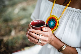 Woman at yoga teacher training drinking tea and meditating