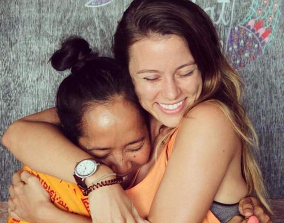 Yoga students hugging in bali during yoga teacher training