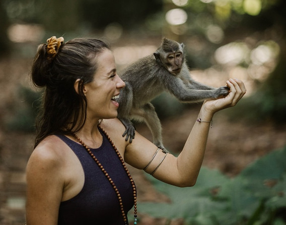 Yoga student with a monkey on her shoulder in bali during yoga teacher training