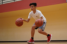 image of a teenager dribbling a basketball using both hands