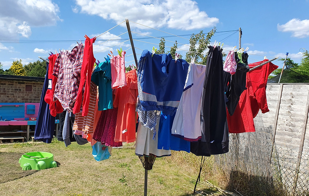 A rotary washing line filled with clothes hanging from it with a blue sky and some clouds.