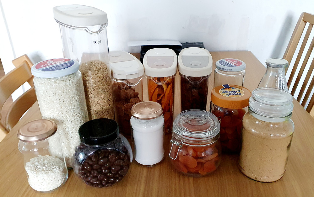 A selections of jars and pots with loose dried goods filling them. The pots and jars are sitting on a wooden table.
