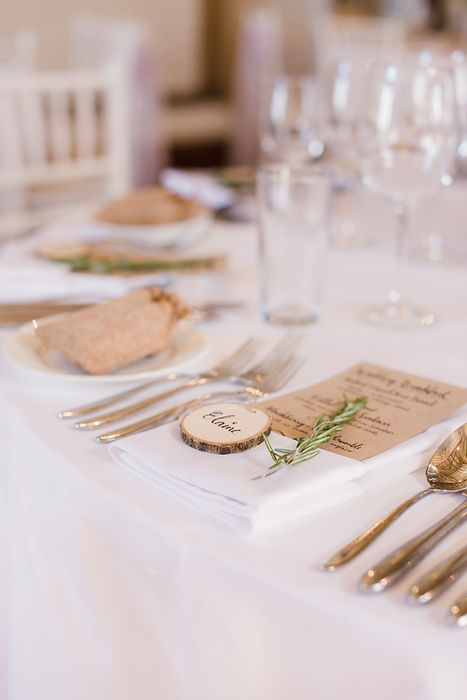 Rustic, natural wedding table setting with wood slice place card, rosemary and handwritten wedding menu