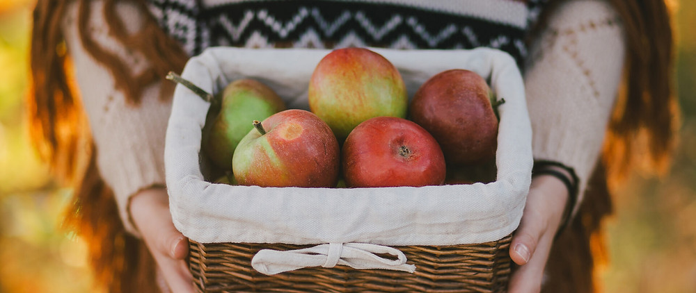 Someone holding a basket of apples for a fall anniversary idea