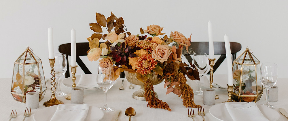 A wedding table with a centrepiece of fall stuff, flowers, candles, etc