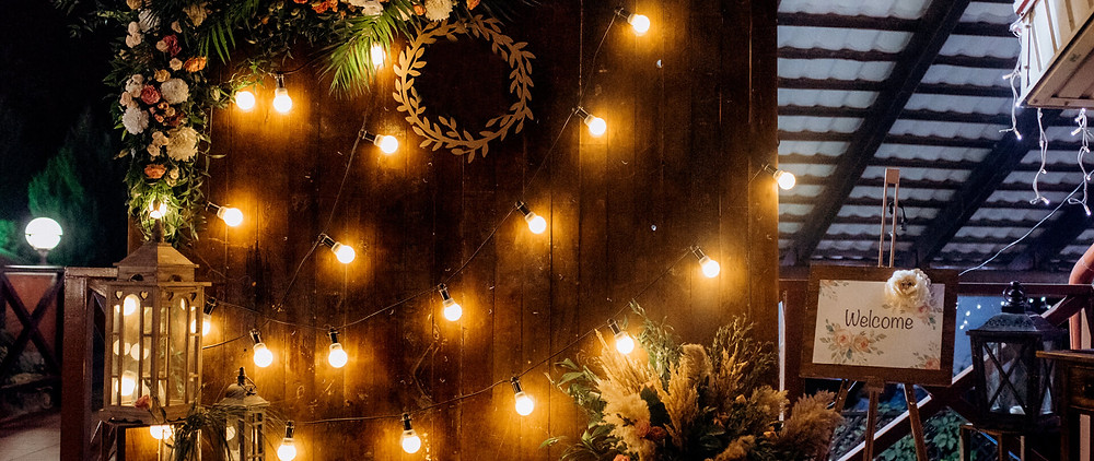 A selfie wall for a fall wedding with lights