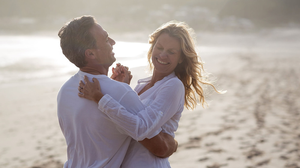A couple dancing on the beach for their 25th wedding anniversary
