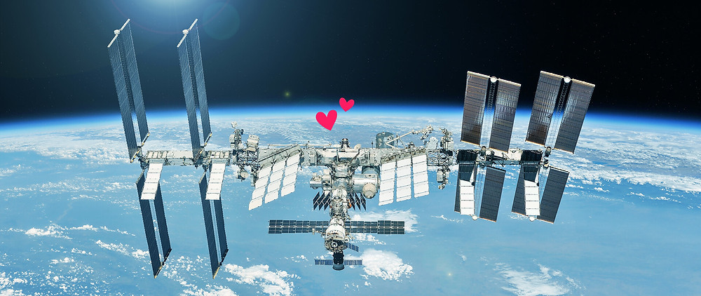 Hearts emerging from a space station with Earth looming behind