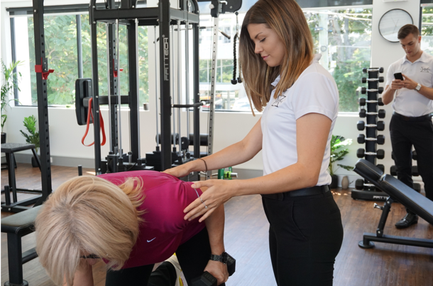 Exercise physiologist instructing women how to lift weight