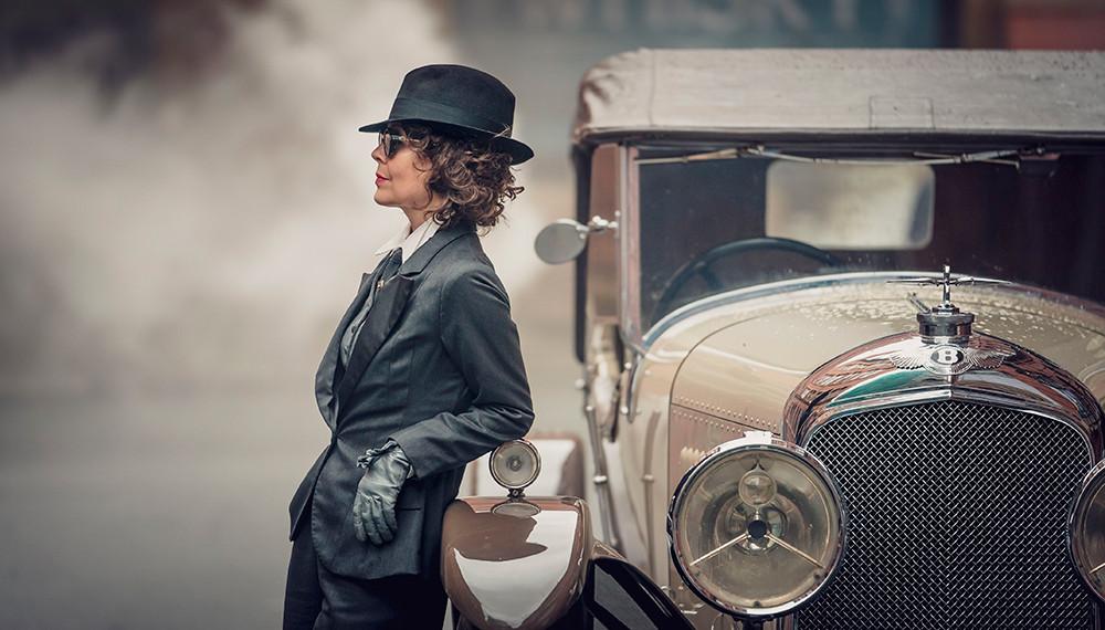 foto da personagem Polly Gray da série Peaky Blinders encostada em um carro