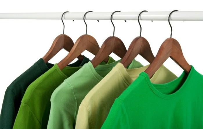 cinco camisetas verdes penduradas em cabides e feitas dentro da moda sustentável