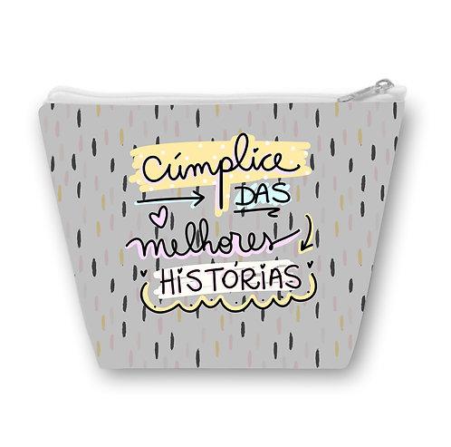 Necessaire com fundo cinza e pequenas estampas e o texto Cúmplice das Melhors Histórias em letras decoradas e coloridas