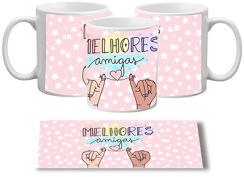 Caneca branca com fundo rosado e o texto Melhores Amigas em letras decoradas e duas mãos com os mindinhos juntos ao centro