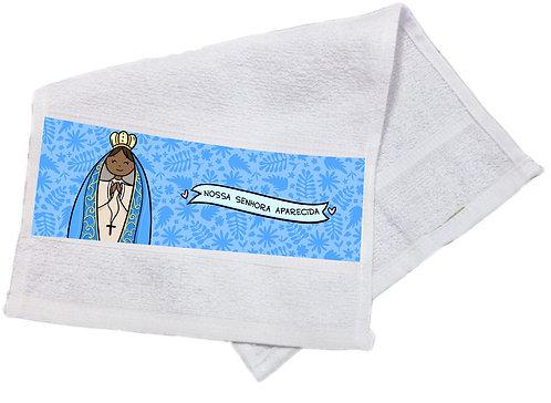 Toalha branca com estampa no barrado, estampa com fundo azul de folhagens e o desenho de N. Sra. Aparecida em versão fofa