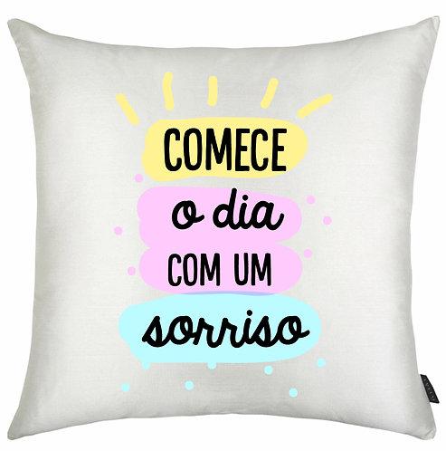 Almofada branca quadrada com a frase Comece o dia com um sorriso em letras pretas e bordas coloridas ao fundo