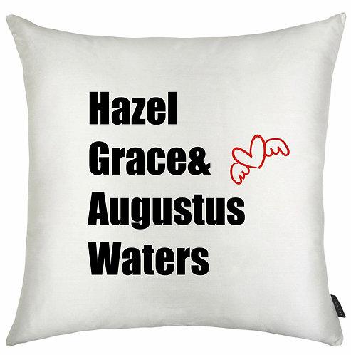 almofada quadrada branca com a escrita Hazel Grace & Augustus Waters e o desenho de um pequeno coração com asas