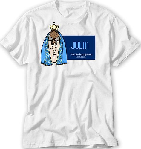 """Camiseta branca, ilustração fofa de N.Sra. Aparecida, um quadro azul ao lado com o nome + """"N. Sra. Aparecida Rogai por Nós"""""""