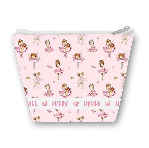 Necessaire rosa com desenho de bailarinas ao fundo e uma faixa na parte inferior com o nome a ser personalizado repetido
