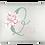 Almofada retangular branca com a Inicial do nome em verde centralizada, um bouquet de flores rosa e o nome escrito em rosa
