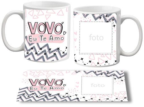 Caneca branca, com fundo geométrico em tons de rosa e cinza, a frase Vovó Eu Te Amo de um lado e uma área para foto do outro