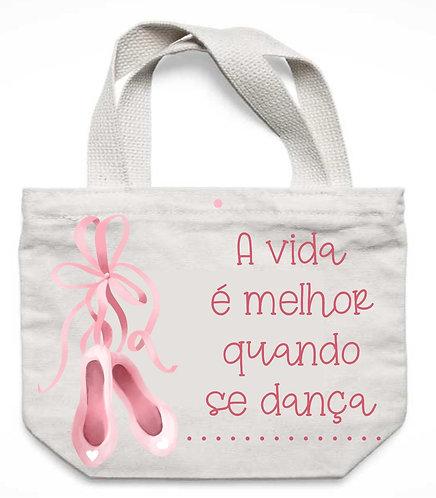"""ecobag branca com a frase """"A vida é melhor quando se dança"""" e um par de sapatilhas rosa ao lado esquerdo"""
