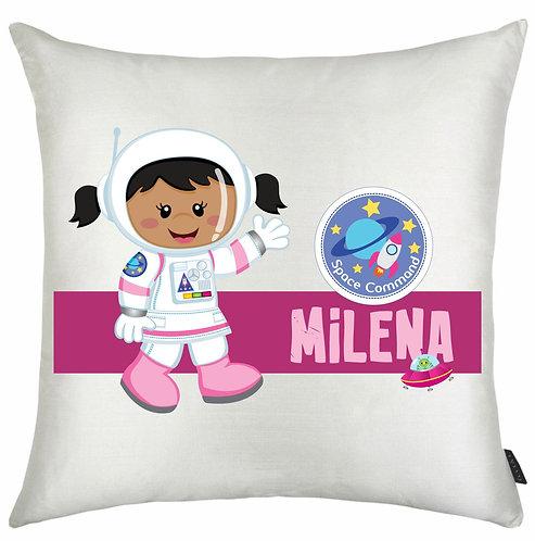 Almofada quadrada branca com o desenho de uma menina negra vestida de astronauta e uma faixa com nome e ícones espaciais