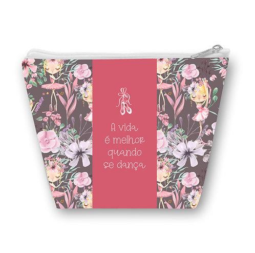 """Necessaire com fundo escuro com bailarinas e flores, uma faixa rosa ao centro com a frase """"A vida é melhor quando se dança"""""""