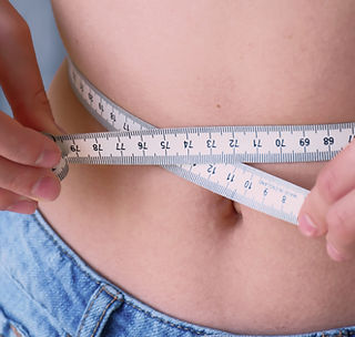 young-girl-measuring-her-waist-with-a-ta